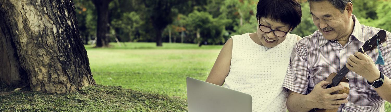 Couple looking at laptop while sitting in park
